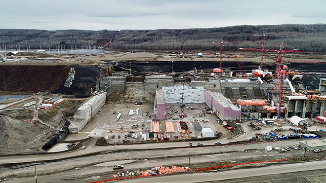 Looking south at the spillways buttress (left) and the Site C powerhouse, under construction (right).