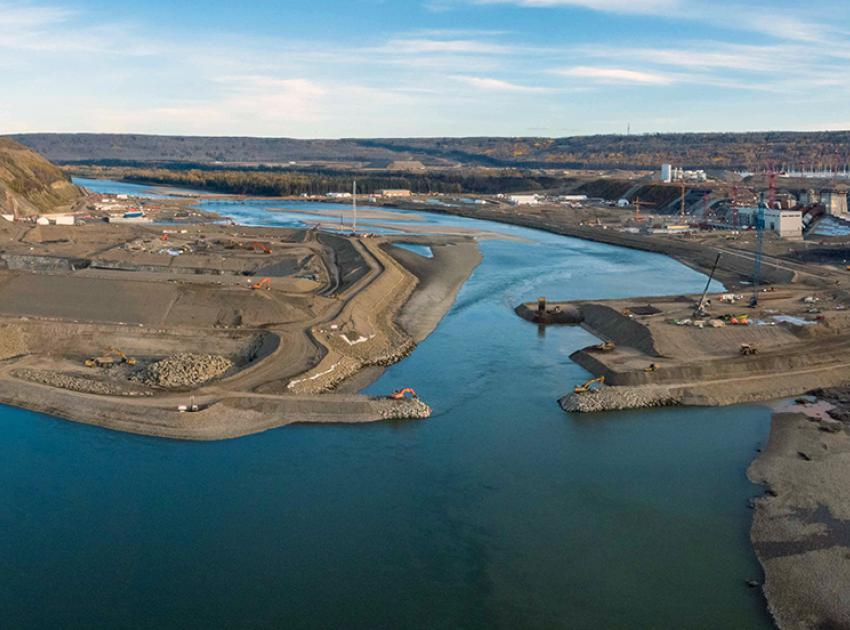 The Peace River continues to flow down the main river channel as well as through the open diversion tunnels as the rockfill berm nears completion. (October 2020)