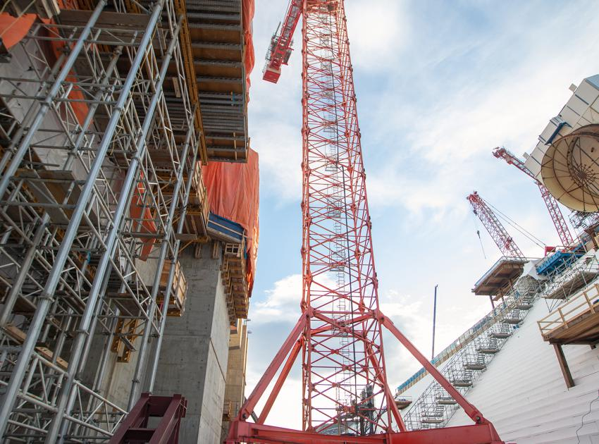 This tower crane has a lifting capacity of 64 tonnes and travels on rails to lift and install the penstock sections. (November 2019)