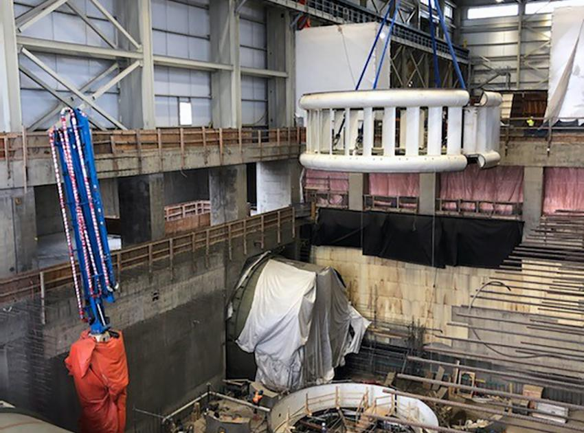 The Unit 1 stay ring is lowered into place using a crane. (February 2021)