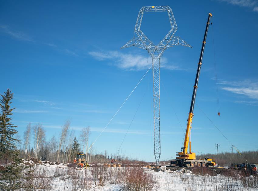 A large crane raises a transmission tower that stands 33 metres tall, as crews tension the Guy-Wires. (Spring 2019)