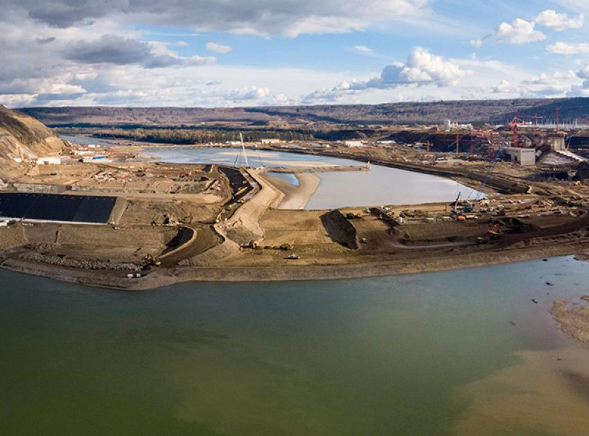 With the rockfill berm and upstream cofferdam complete, the Peace River flows through Site C's twin diversion tunnels at centre-left. (October 2020)