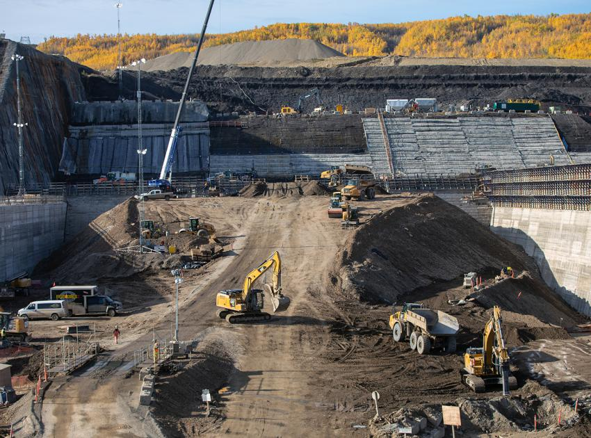 A ramp is constructed to provide access for trucks onto the spillway buttress to deposit roller-compacted concrete. (September 2019)
