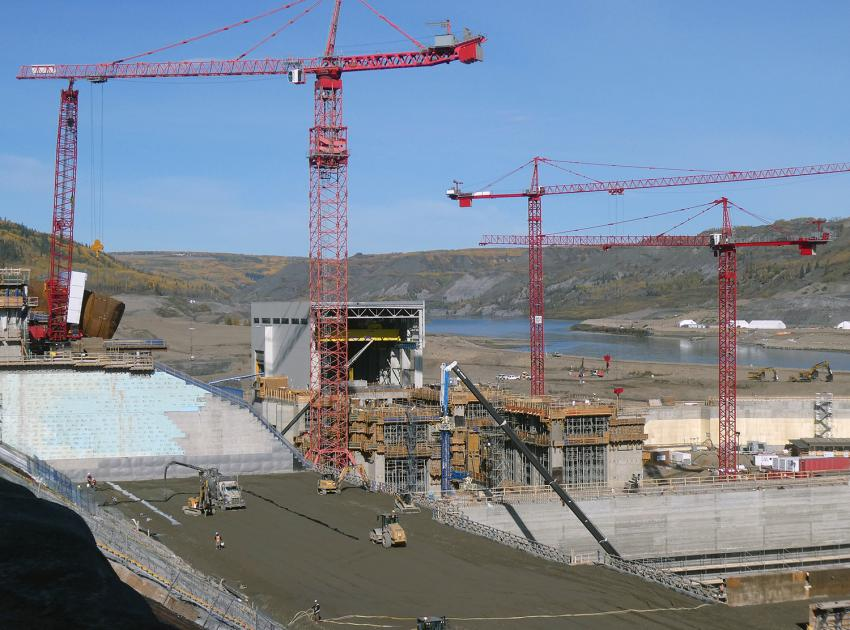Roller-compacted concrete is placed on the spillway buttress, with the powerhouse in the background. (September 2019)
