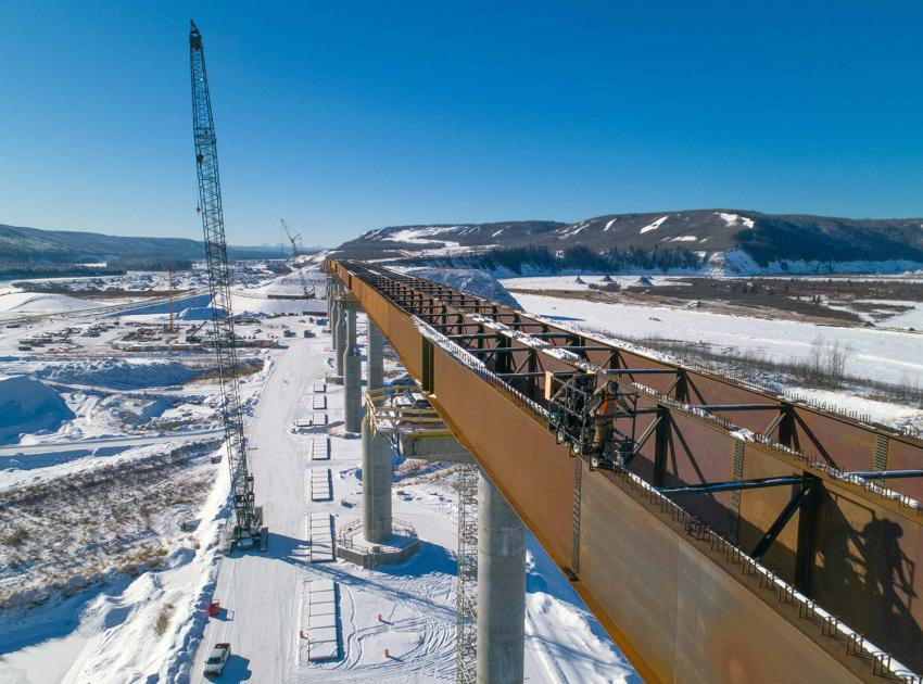 Crews at the Halfway River bridge use a survey buggy to measure the angle of the bridge girders before installing the bridge deck. All twelve bridge piers are complete and steel girders are being installed on top. (February 2021)