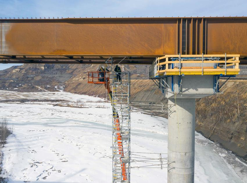 Girder installation is complete, and workers remove scaffolding from the Halfway River bridge. (March 2021)