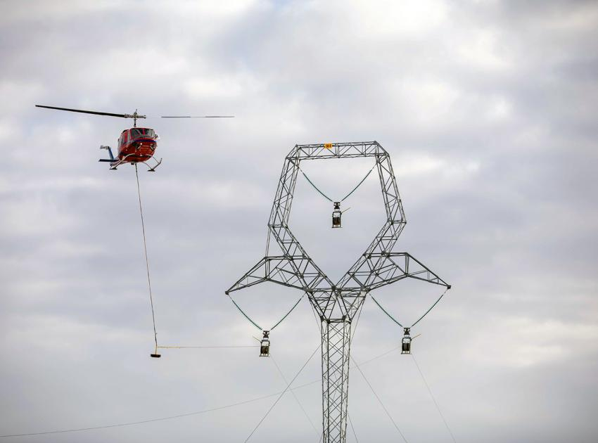 As part of transmission line installation, a helicopter pulls the sock line through the traveller, like a pulley. (March 2020)