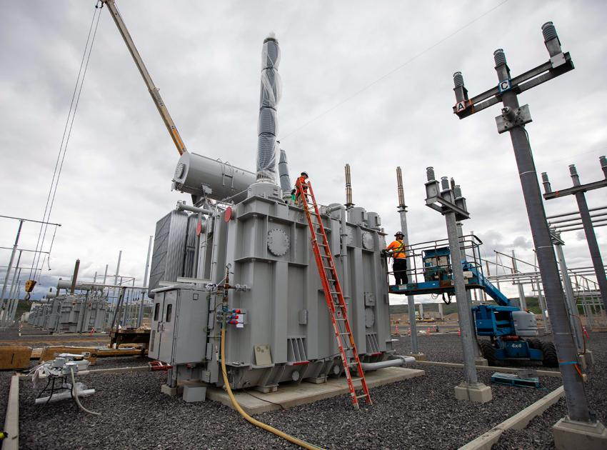 Workers connect a transformer for the Peace Region Electrical Supply (PRES) system – located at the Site C substation. (June 2020)
