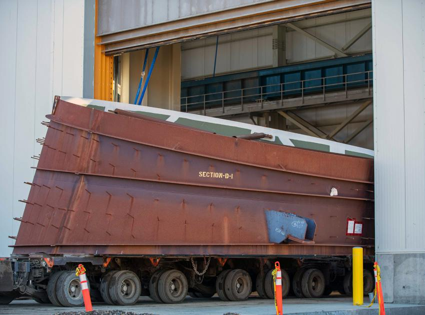 The 10-metre-wide, 20 tonne, draft-tube elbow is delivered to the main service bay in the powerhouse. Each penstock will be made of 14 segments, welded together at the dam site. (October 2020)