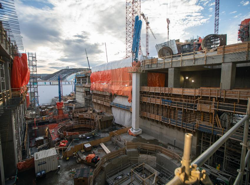 Construction of the powerhouse continues with installation of penstock units at the top of the structure. (November 2019)