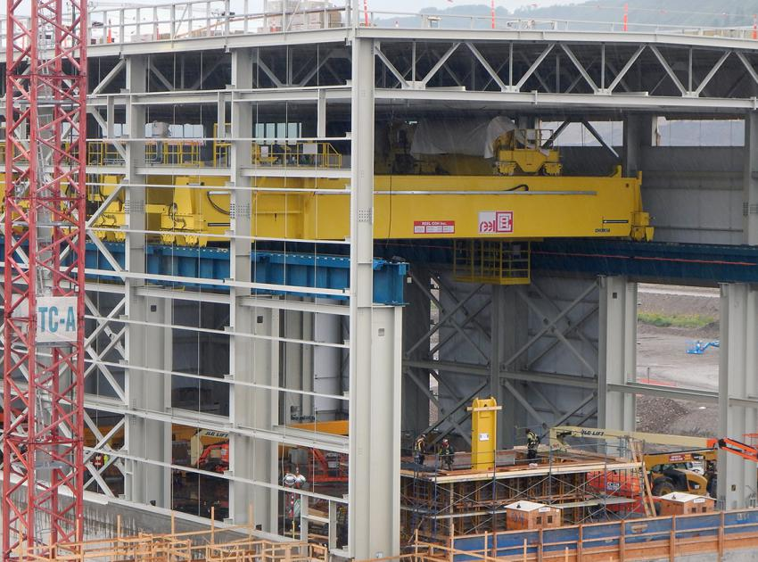 A large yellow powerhouse bridge crane loads blocks of up to 320 metric tonnes inside the main service bay. (July 2019)