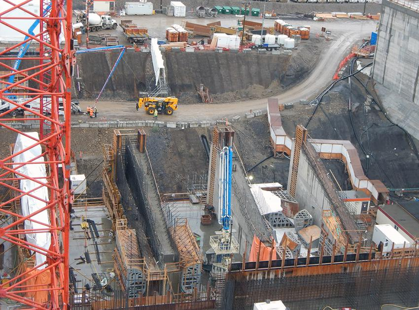 Rebar placement and wet curing of concrete are steps in construction for the Unit 5 tail race piers in the powerhouse. (July 2019)