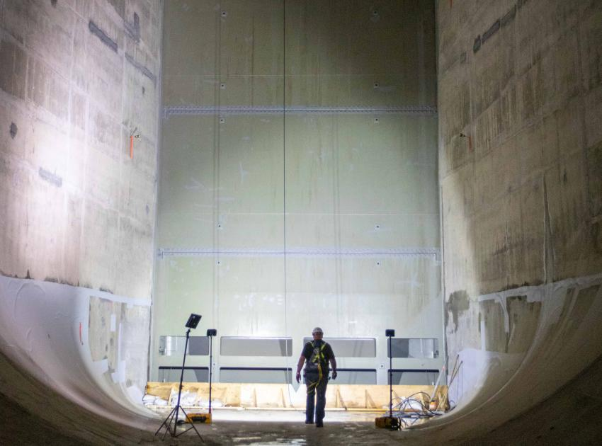 A worker inspects a gate in a diversion tunnel as part of wet testing ahead of river diversion this fall.